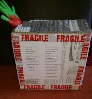Cardboard box with fragile tape around it and a green and red hand out of lid at side. Poem printed on paper stuck on front.